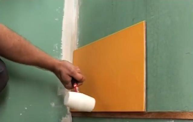 Придавливаем плитку к стене слегка постукивая киянкой